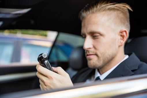 Man sitting inside car looking at breathalyzer test.