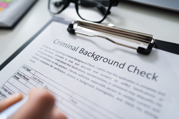 Close-up Of Hand Filling Criminal Background Check Application Form With Pen